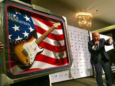 Live Auctioneer for Fundraising Auctions Jason Kazanis in action auctioning off autographed Bruce Springsteen Guitar at fundraising event.